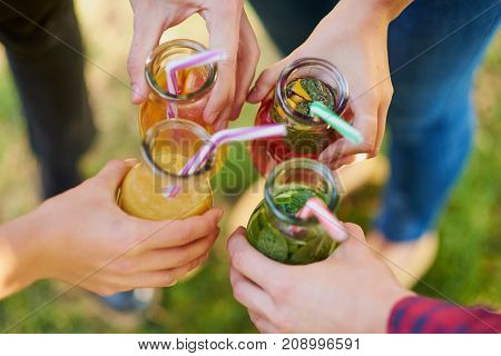 Group of people celebrate with detox juice cocktailss on green nature background. Diet on the go, well being and weight loss, superfoods, health, vegetarian food concept
