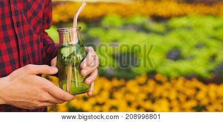 Healthy lifestyle. Unrecognizable young man with detox cocktail in summer, on green nature background. Diet, well being and weight loss concept