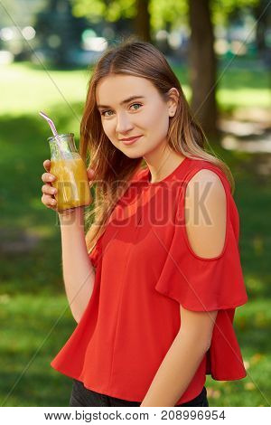 Healthy lifestyle. Unrecognizable young woman with yellow berry detox smoothie in summer, on green nature background. Diet, well being and weight loss concept