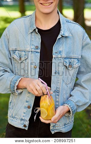 Healthy youth lifestyle. Happy hipster guy with detox with sweet citrus detox tea or orange juice in summer, on green nature background. Diet, well being and weight loss concept