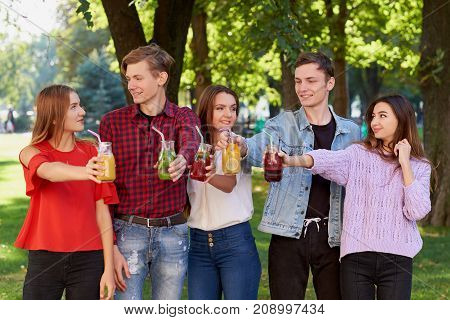 Healthy nutrition. Group of friends drinking fresh juice detox on green nature background. Youth lifestyle, vegetarian diet to go, fitness food, successful weight loss concept