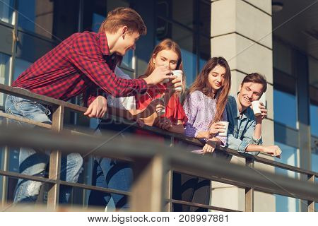 Students enjoying cup of coffee to go on street. Young people in the morning outdoor with cup of energy drink