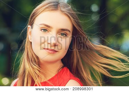 Face of happy beautiful woman with flying hair posing on the street in summer in red dress. Friendly calm blonde girl looking at camera with cheerful confident expression
