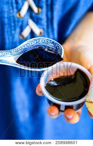 Hands Holding Black Chinese Herb Jelly Called Guiling Gao, A Chinese Herb-Made Dessert.