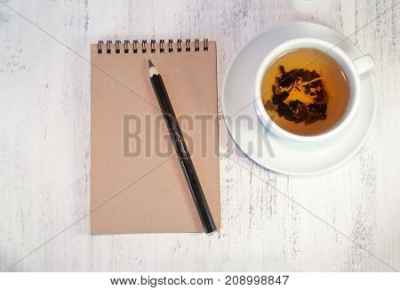 Notepad For Notes Or For Sketches On A Wooden Table. Near The Black Pencil And Cap Of Tea.