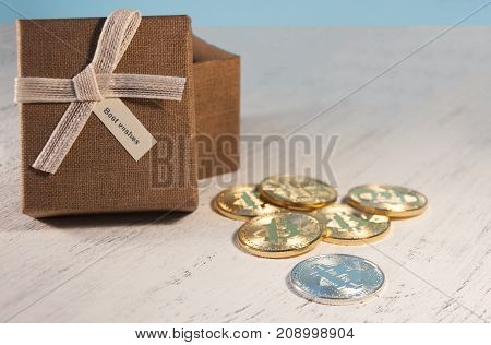 A Brown Gift Box And A Beige Ribbon With A Label On A Light Background. A Christmas Gift. Coin Bitco