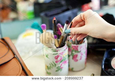 A professional make-up artist picks up brush