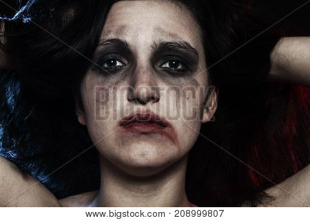 sad woman with smeared make up in dark