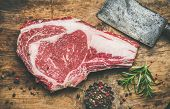 Flat-lay of raw uncooked prime beef meat dry-aged steak rib-eye on bone with seasoning and chopper knife on rustic wooden board background, top view. Meat high-protein dinner concept poster