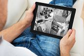 Close-up Of A Man Sitting On Sofa And Monitoring Video Footage On Tablet At Home poster