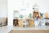 Plush toys and pillows on wooden handmade shelves in child's room with posters on wall poster