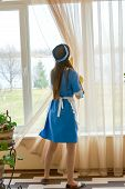 Housemaid near a window. Maid at work. poster