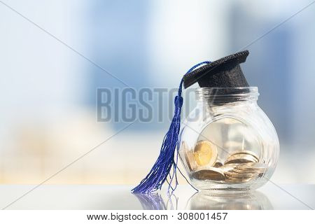Graduation Hat With Blue Tassel On Top Of Glass Jar Or Piggy Bank Filled With Coins On Modern City B