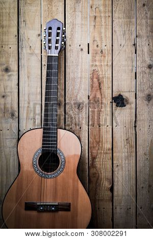 Acoustic Guitar On Vintage Style Wood Background. Copy Space With Musical Guitar Instrument
