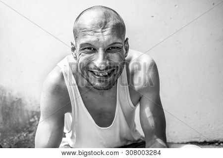 Happy Homeless, Young Positive Skinny Anorexic Bald Happy Smiling Homeless Man Sitting On The Urban