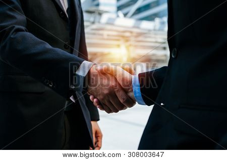 Deal. Close Up Two Young Businessman Investor In Suit Shaking Hands With Partner During New Project