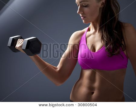 Studio photo of attractive young woman lifting dumbbell.