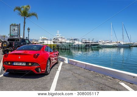 Puerto Banus, Spain - May 26, 2019: A Red Ferrari California In Front Of Luxury Yachts At Puerto Ban