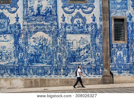 Porto, Portugal: Blue Ceramic Tiles Azulejo On Beautiful Cathedral Wall, And Lonely Walking Man On S