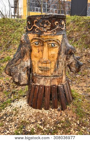 Wooden Sculpture In Park In Shape Of Woman's Face