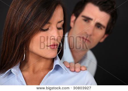 Concerned man touching his wife's shoulder