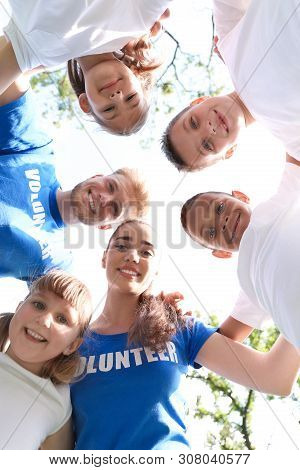 Low Angle View Of Volunteers Huddling With Kids In Park