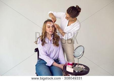 Beautician Aesthetician Glues Kinesio Tape On The Face