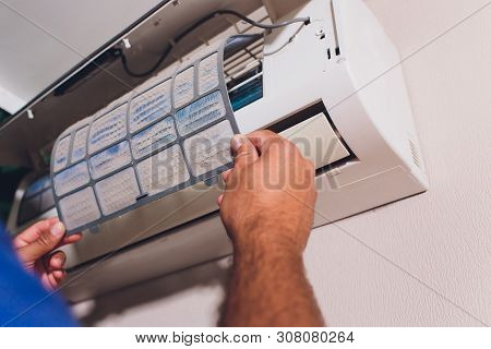 Male Technician Cleaning Air Conditioner Indoors. Service