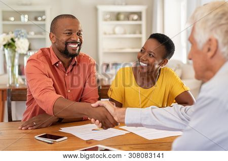 Mature black husband shaking hands with senior agent on taking loan. Happy african couple sealing with handshake a contract with financial advisor for investment. Man making sale purchase deal.