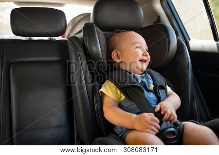 Portrait of cute smiling toddler sitting in car seat and looking outside the window. Little boy sitting in safety chair with copy space. Happy child having fun in safety car seat enjoy the travel.