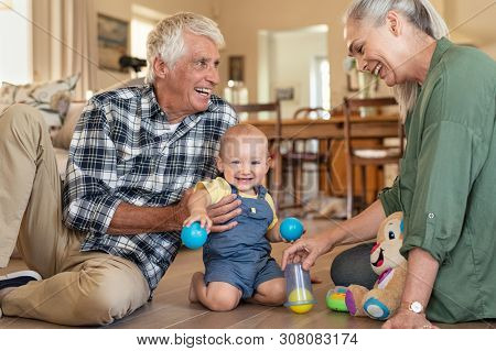 Smiling grandchild with grandparents playing with balls at home. Happy grandson with grandmother and grandfather playing with toys on floor at home. Senior woman and old man playing with little  boy.