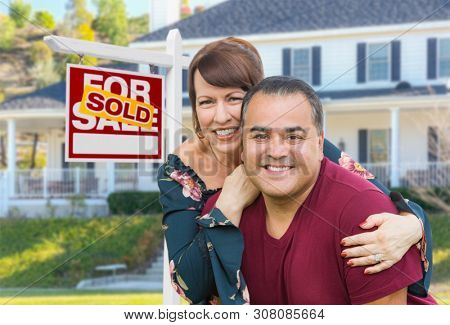 Mixed Race Young Adult Couple In Front of House and Sold For Sale Real Estate Sign.