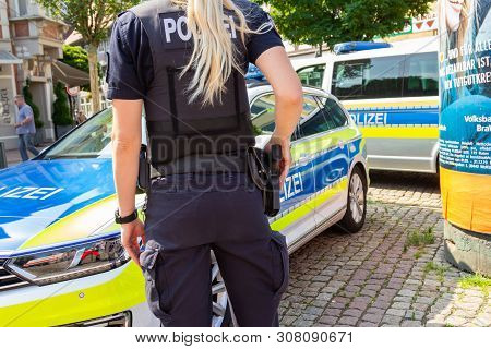 Peine / Germany - June 22, 2019: German Female Police Officer Stands In Front Of Police Cars At Publ