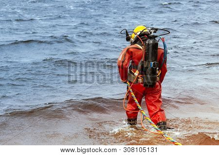 A Professional Diver In An Orange Wetsuit Enters The Water For Deep-sea Work.