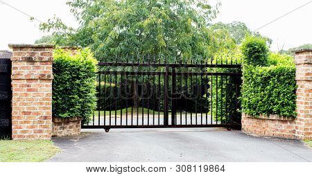 Black Metal Driveway Property Entrance Gates Set In Brick Fence With Garden Shrubs And Trees In Back