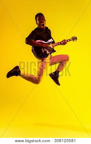 Young African-american Musician Playing The Guitar Like A Rockstar On Yellow Background In Neon Ligh
