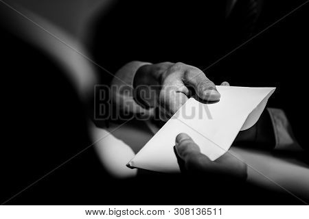 Businessman giving bribe money in the  envelope to partner in a corruption scam with black and white tone poster