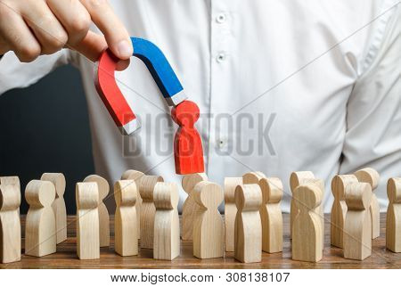 Businessman Pulls Out A Red Figure Of A Man From The Crowd With The Help Of A Magnet. Leader Manages