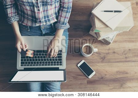 Top View Of Woman Shopping Online With Credit Card Via Laptop Computer From Home On Wooden Floor Wit