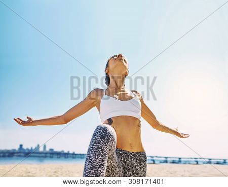 Outdoors Portrait Of Young Slim Athletic Woman Standing In Yoga Asana With Raised Arms On The City A