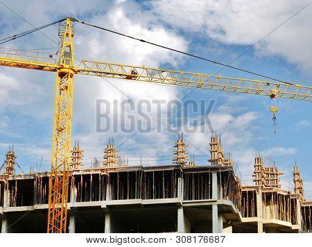 Construction Crane Near Unfinished Bulding Against Blue Sky. Construction Site. Construction In Prog
