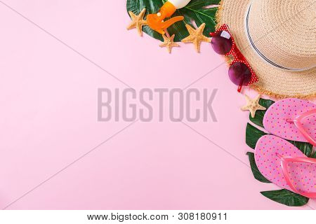 Beach Accessories With Straw Hat, Sunscreen Bottle And Seastar On Pink Background Top View With Copy