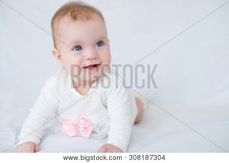 Cute Baby With Blue Eyes In White Dress With Pink Bow Lying On Her Stomach Looking At Camera, White