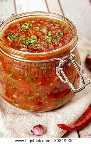 Tomato Salsa In A Glass Jar. Homemade Spicy Tomato Sauce With Chilli, Garlic And Lime. Close Up And