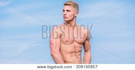 Sport and bodycare. Muscular masculine guy look confident. Man sexy muscular bare torso stand outdoor blue sky background. Man muscular torso stand confidently. Sportsman muscular torso posing poster