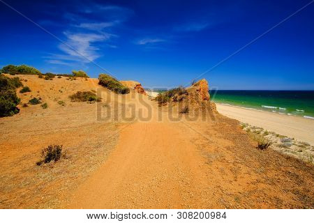 View on the beautiful beach Praia da Rocha Baixinha Nascente with beautiful red sandstone sliffs and golden sand. Region Faro, Algarve. Vacation in Portugal. poster