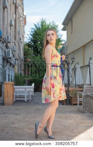 A Young Girl With Long White Curls In A Dress Walks Through The Old Town In The Summer. Girl In A Fl