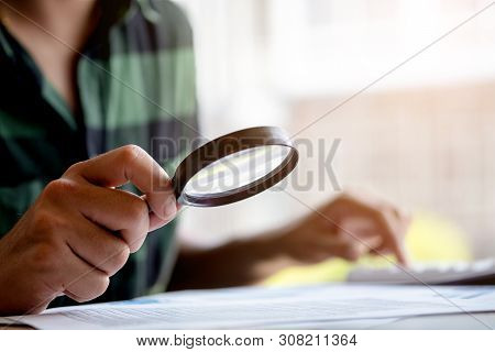 Businessman Looking Through A Magnifying Glass To Documents. Business Assessment And Audit. Magnifyi