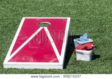 Red Corn Hole Game With White Stripes On A Green Turf Field With Blue And Red Bean Bags In Container