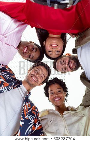 Low angle view of team of diverse business people standing in huddle in a modern office